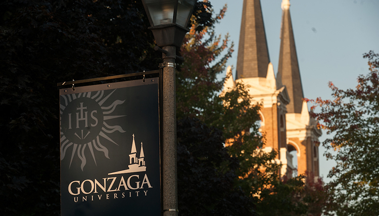 The morning sun lights up a Gonzaga sign and the steeples behind.