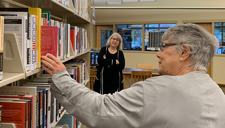 woman pulls book from shelf at library
