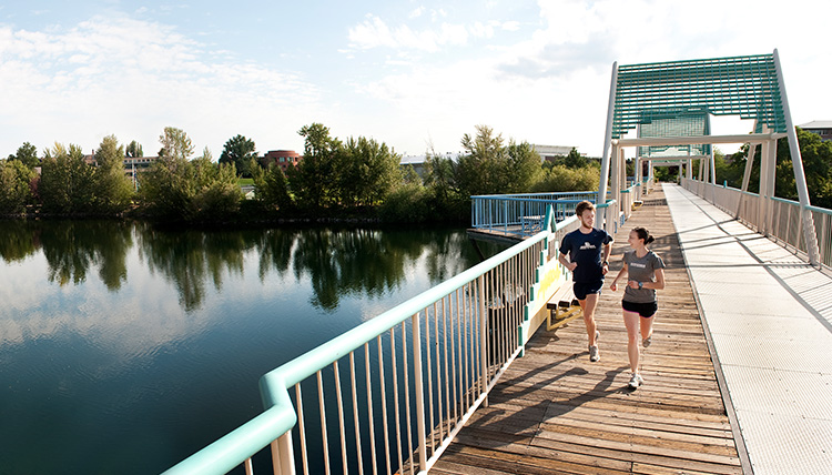 Students running on bridge across Spokane River