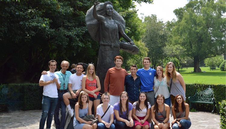Study Abroad student group posing with a statue