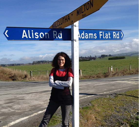 Alison McCulloch, Gonzaga Philosophy graduate, stands in front of a street sign bearing her first name.