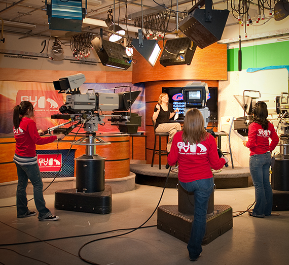 Broadcast journalism students recording video in a news studio setting.