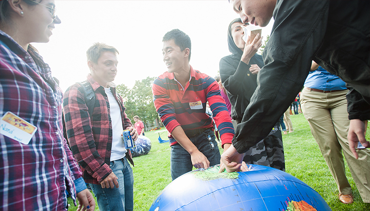 Students point at country locations on a globe.