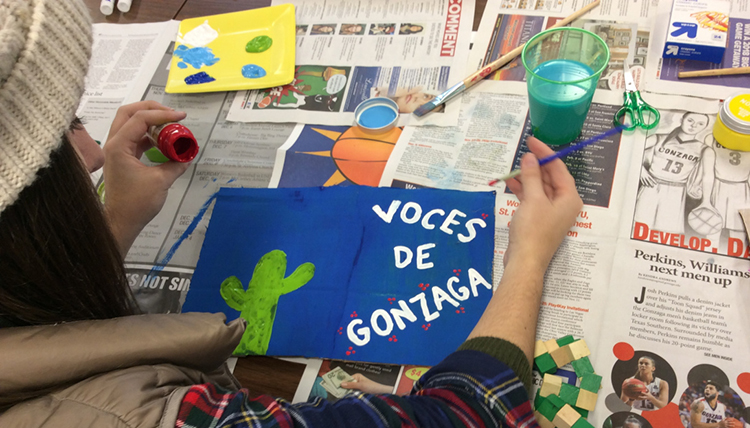 Student artist painting 'Voces de Gonzaga' on paper.