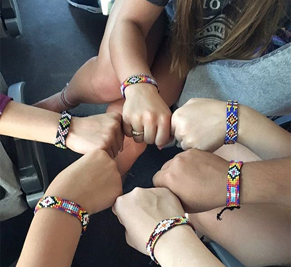 Hands arranged in a circle with bracelets made at summer camp