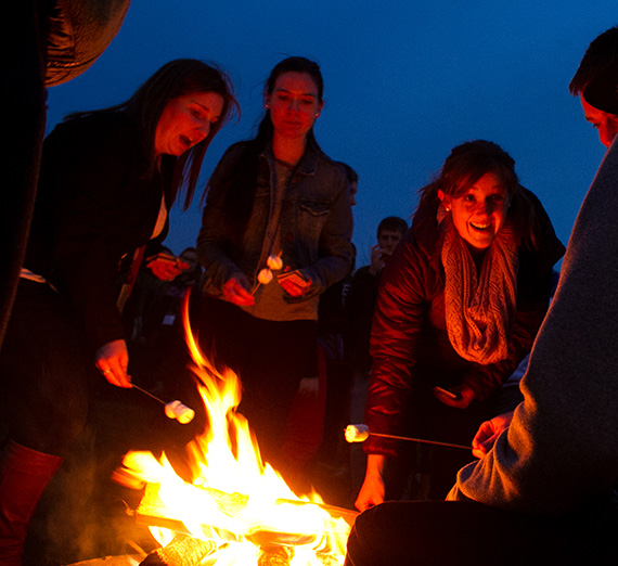 Students gathered around a campfire roasting marshmallows.