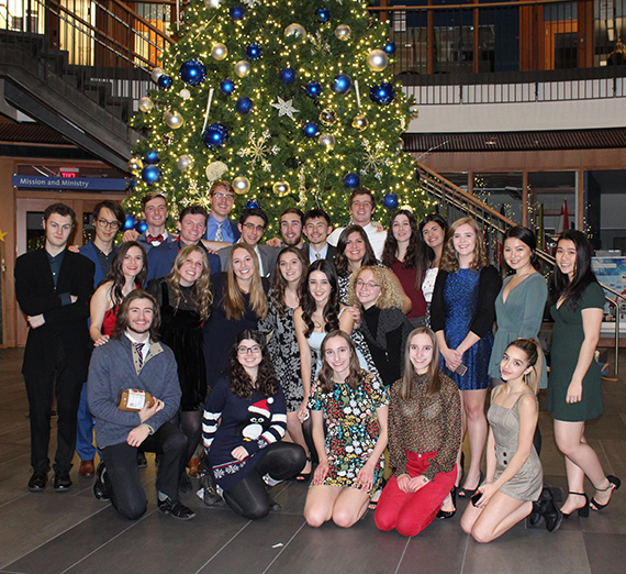 Large group of students posed for a photo in front of a decorated Christmas tree.