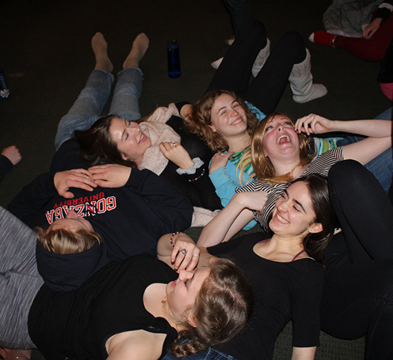A cluster of students laying on the floor in laughter.