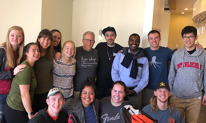 A group of men and women - students, a professor, a priest, and an employee at Homegirl Café - smile for a photo at Homeboy Industries