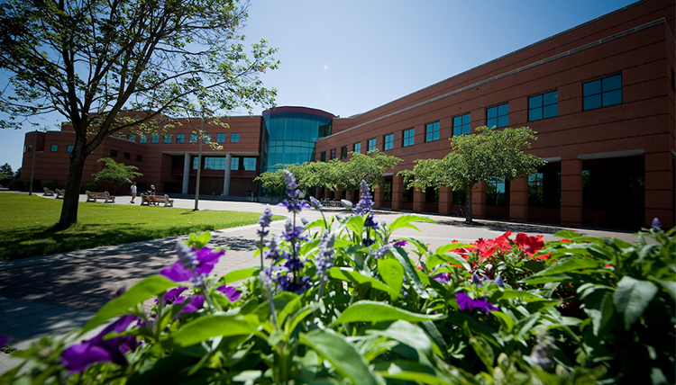 Image of flowers in front of Foley Center Library on a sunny day