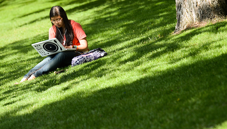 A student studying outside on the green grass