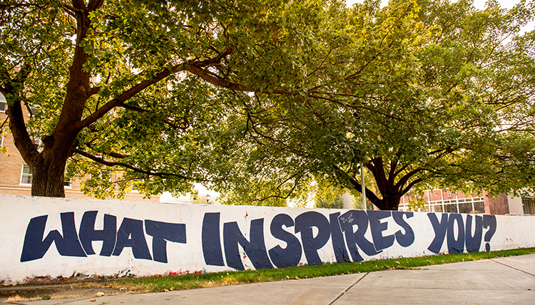 Concrete wall with words painted on. It reads, what inspires you?