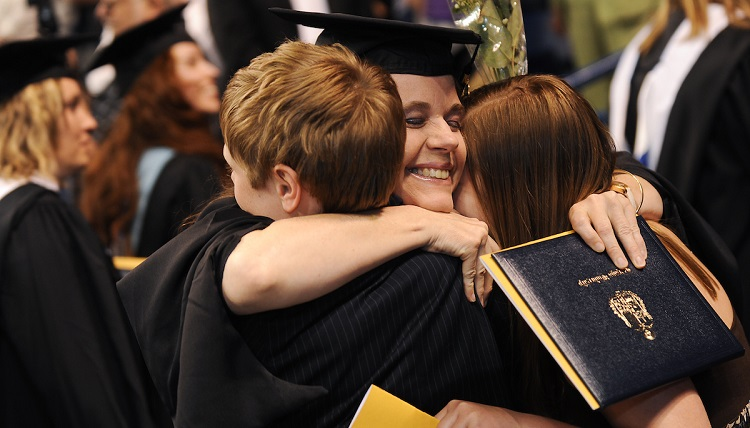 A graduate embraces her children after receiving her degree during the Graduate Commencement ceremony.