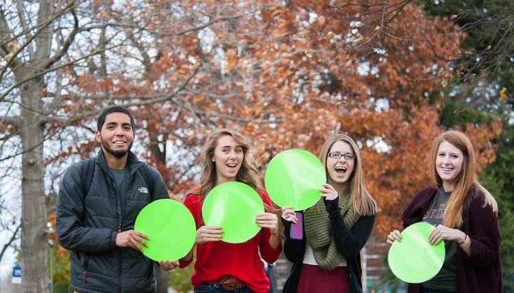 Students hold up green dots as a symbol of being designated drivers.