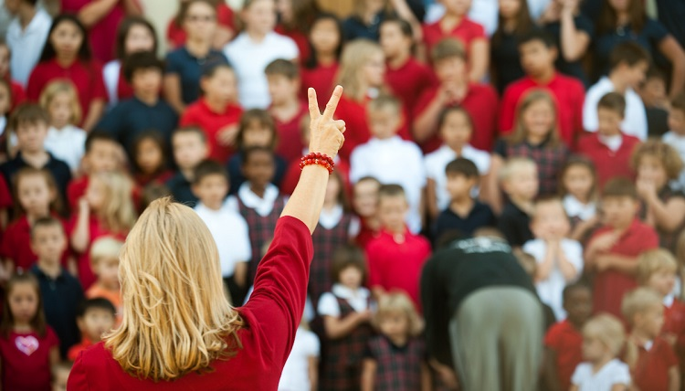 A teacher holds up a peace sign in front of young students.