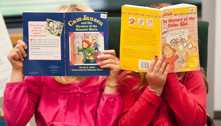 Two children reading books.