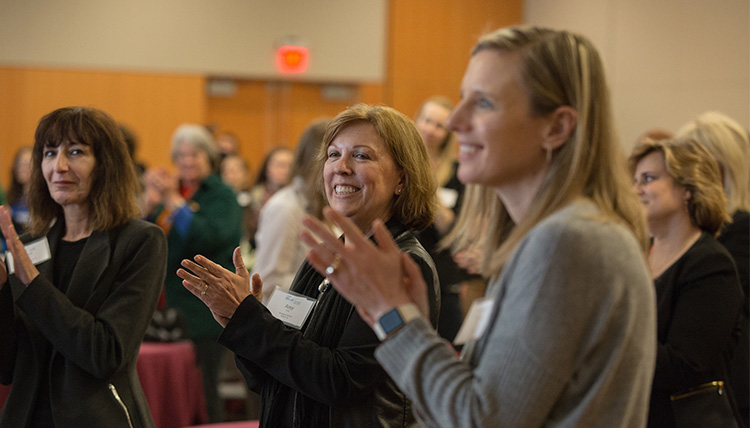 Women clapping at an event during the 2017 Women in Leadership Conference.