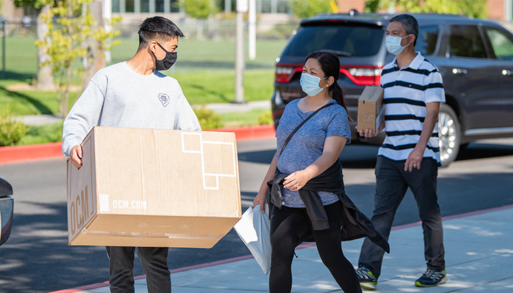 a student and parents carry items to dorm
