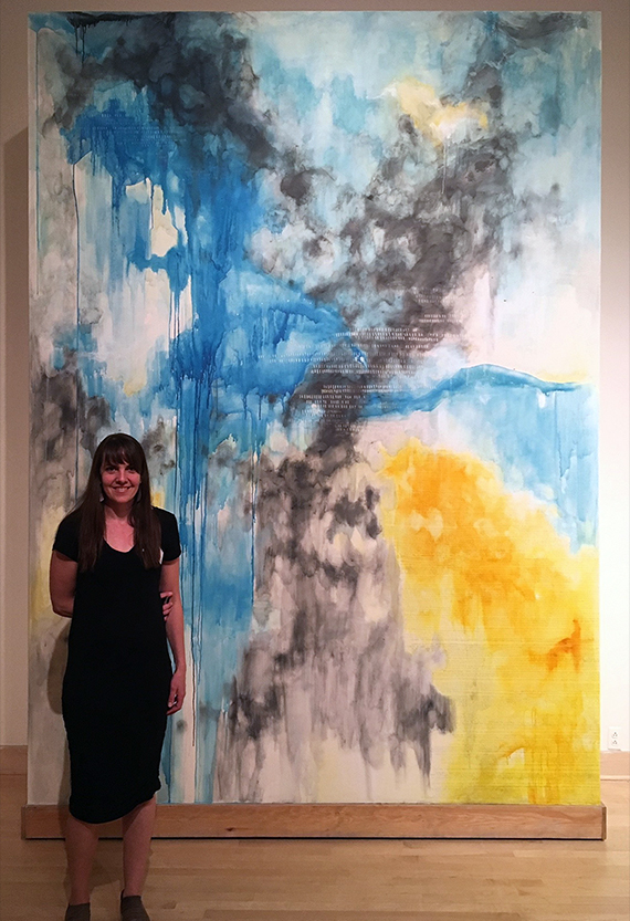 Jen Erickson stands next to her 8 foot by 11 foot artwork.