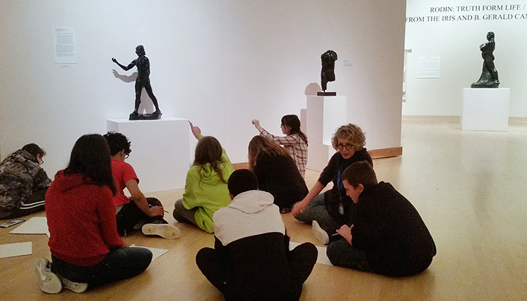 Middle school students sit on the floor of the museum discussing bronze art  on display.