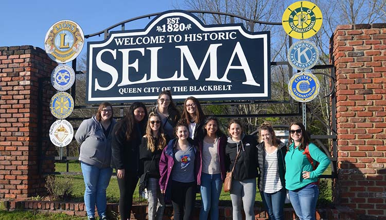 Students posing in front of a sign that says 'Welcome to Historic Selma'