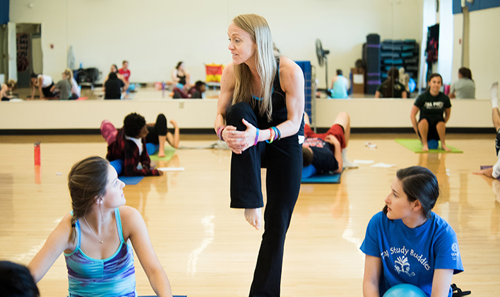 Students in a fitness class pay attention as their instructor demonstrates a correct posture to them