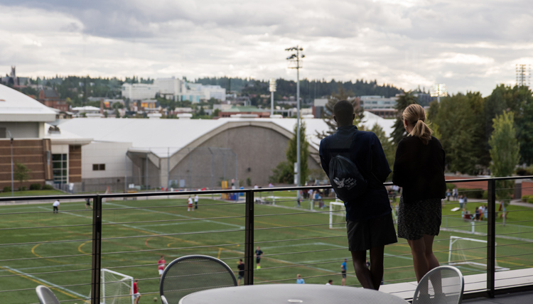 Two GU students stand on Hemmingson balcony overlooking mulligan turf field