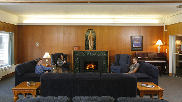 Students sitting on couches around fireplace in residence hall common area.