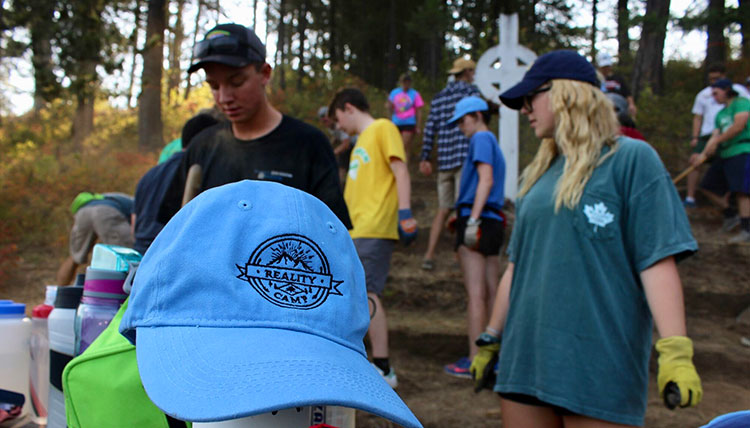 A stack of Reality camp hats sit in the foreground while students volunteer