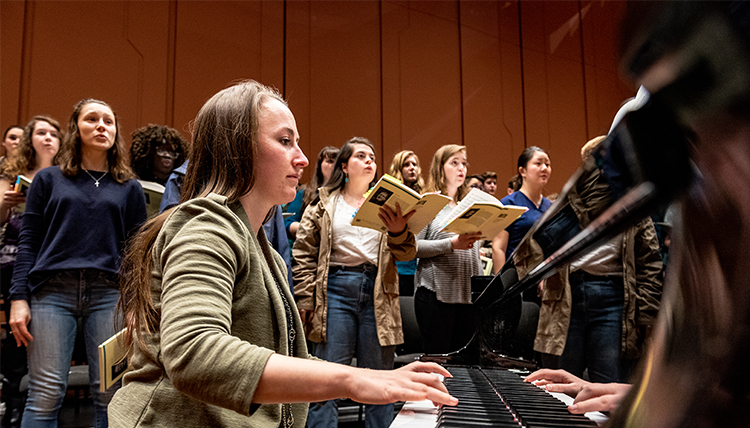 student pianist with choir in background