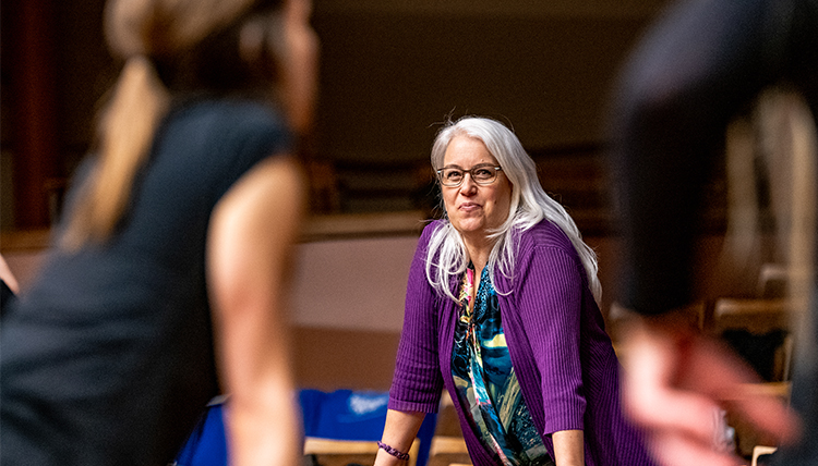 dance director Suzanne Ostersmith leans on stage with student dancers