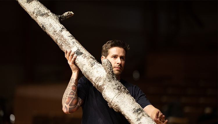 set technician Courtney Smith carries a tree trunk