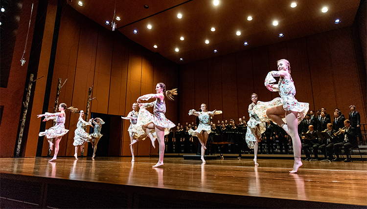 dancers on stage with musicians in the background