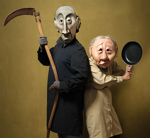 performers with masks dresses as the Grim Reaper and an elderly woman with an iron skillet