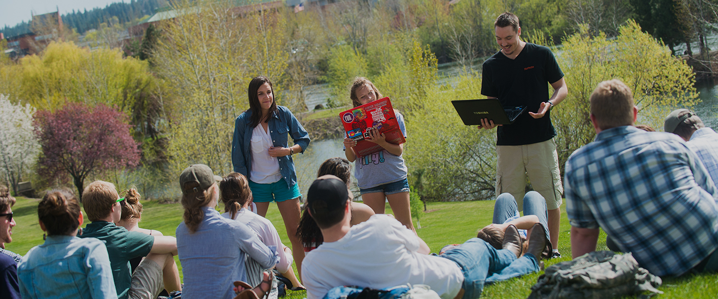 Students give a presentation on the lawn in front of Lake Arthur