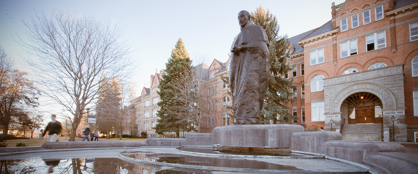 Statue of Saint Ignatius Loyola in foreground with Gonzaga University College Hall in the background.