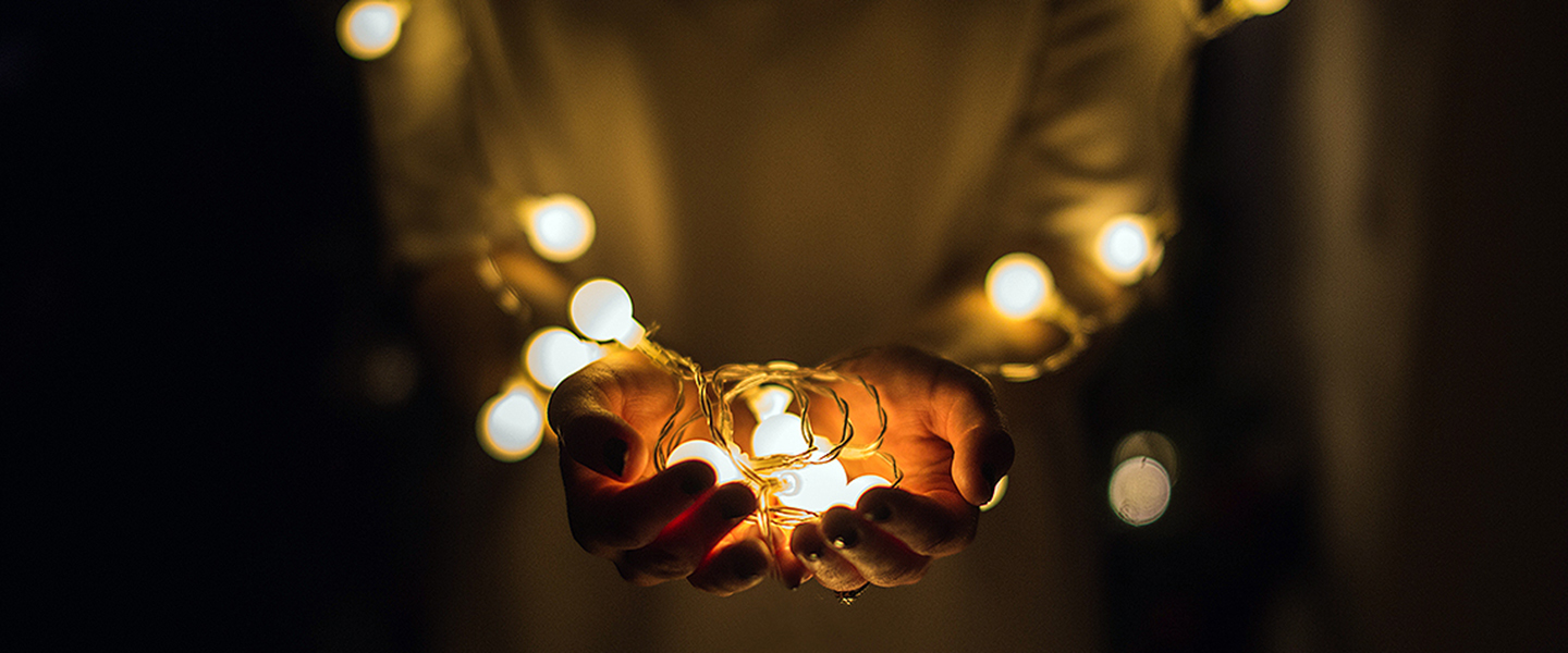 Decorative image, hands holding small lightbulbs