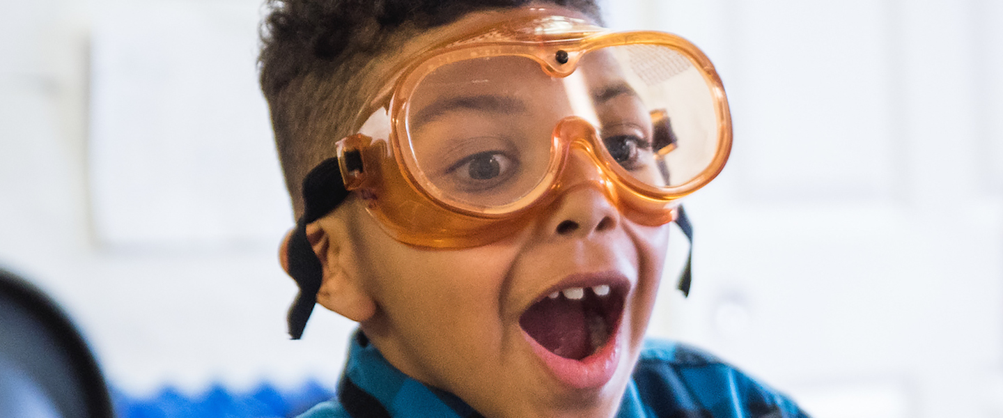 Close-up face of elementary student with science safety glasses.