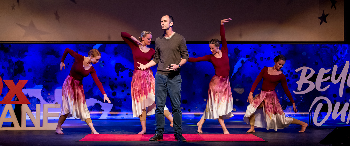 speaker with dancers on stage at TEDx event