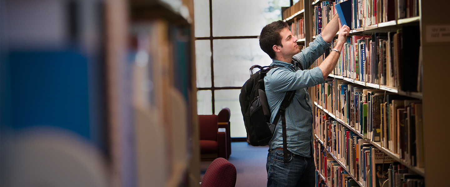 Student browsing library stacks