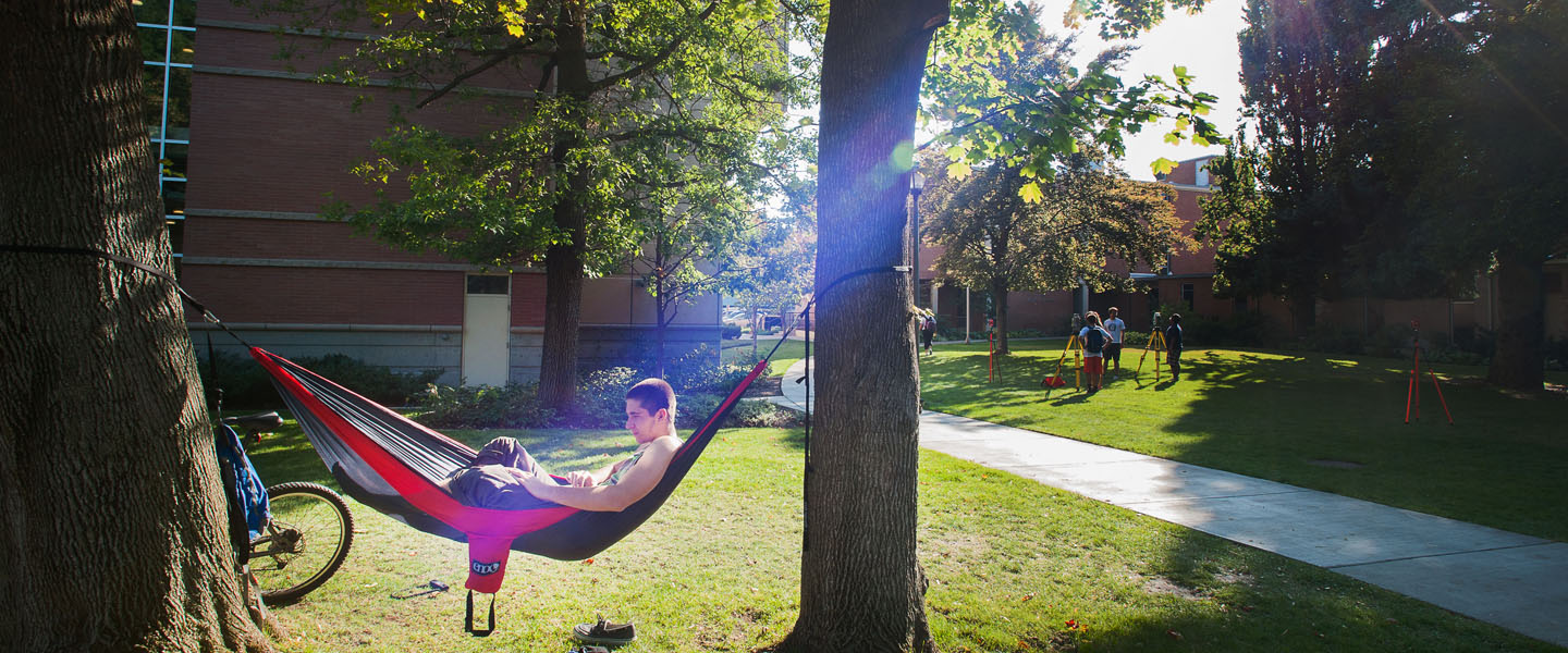 Student in hammock on campus