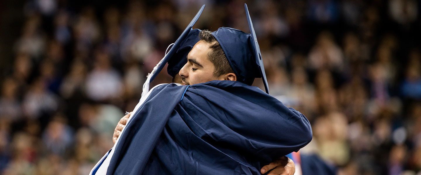 grads hug at commencement