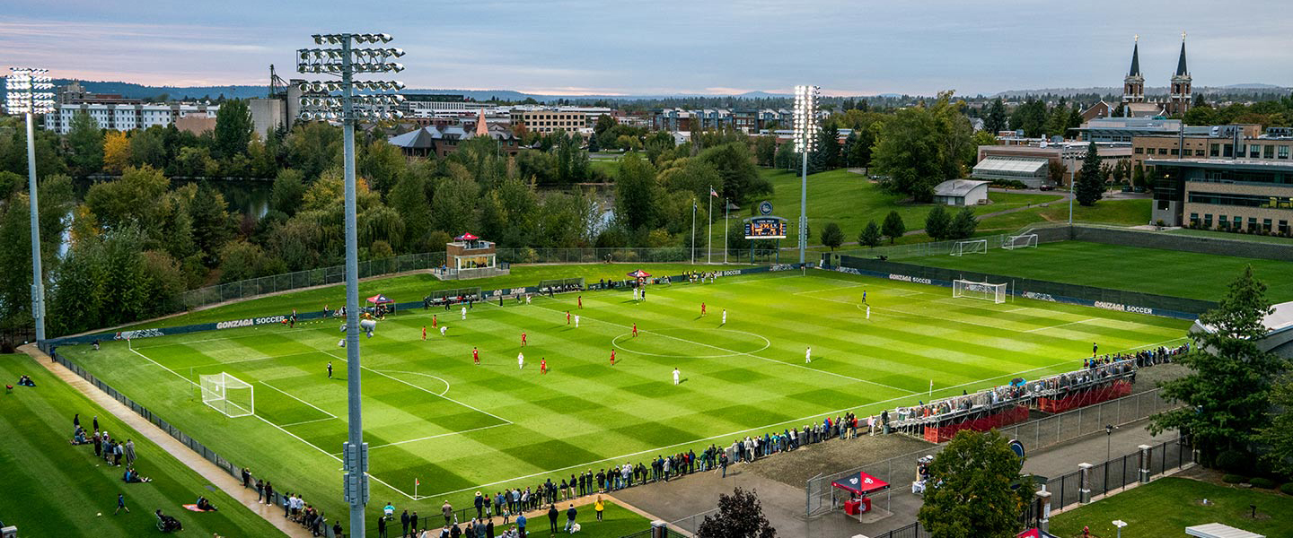Aerial photo of Luger field at dusk with St. Aloysius church in the background during a soccer game