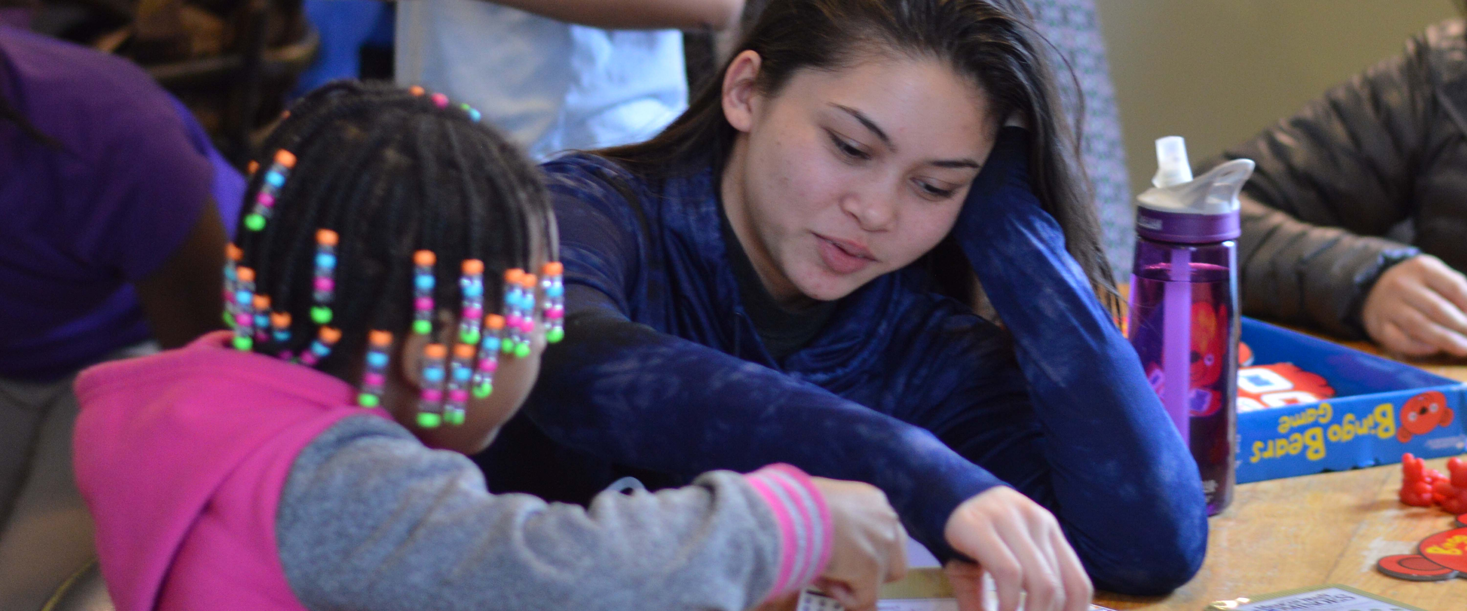 Gonzaga student playing a board game with youth