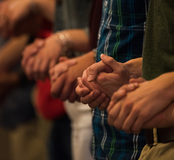 Community members hold hands in prayer for Mass of the Holy Spirit.