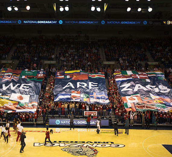 A banner that reads We Are Gonzaga is held by students at halftime during a basketball game.