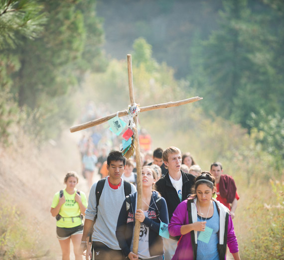 Student walking outdoors with cross