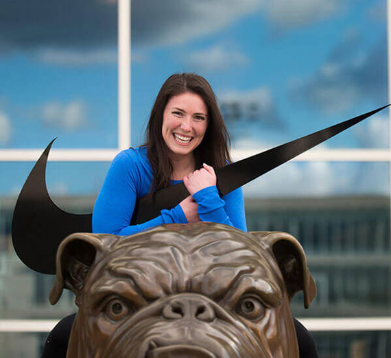 Alumna Sara Wedland ('15 '15, B.Ed. Sport Management, B.A. Applied Communications) holding Nike logo on top of bronze Spike the bulldog statue