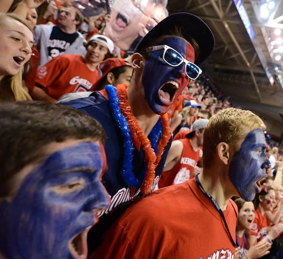 Gonzaga University students with their faces painted cheering in the Kennel Club student section at a basketball game