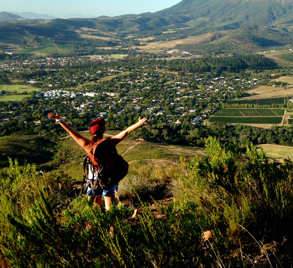A study abroad student hiking above a green valley.
